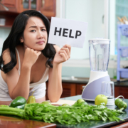 Pretty Asian woman frowning and holding paper saying Help standing with heap of green vegetables and blender in kitchen